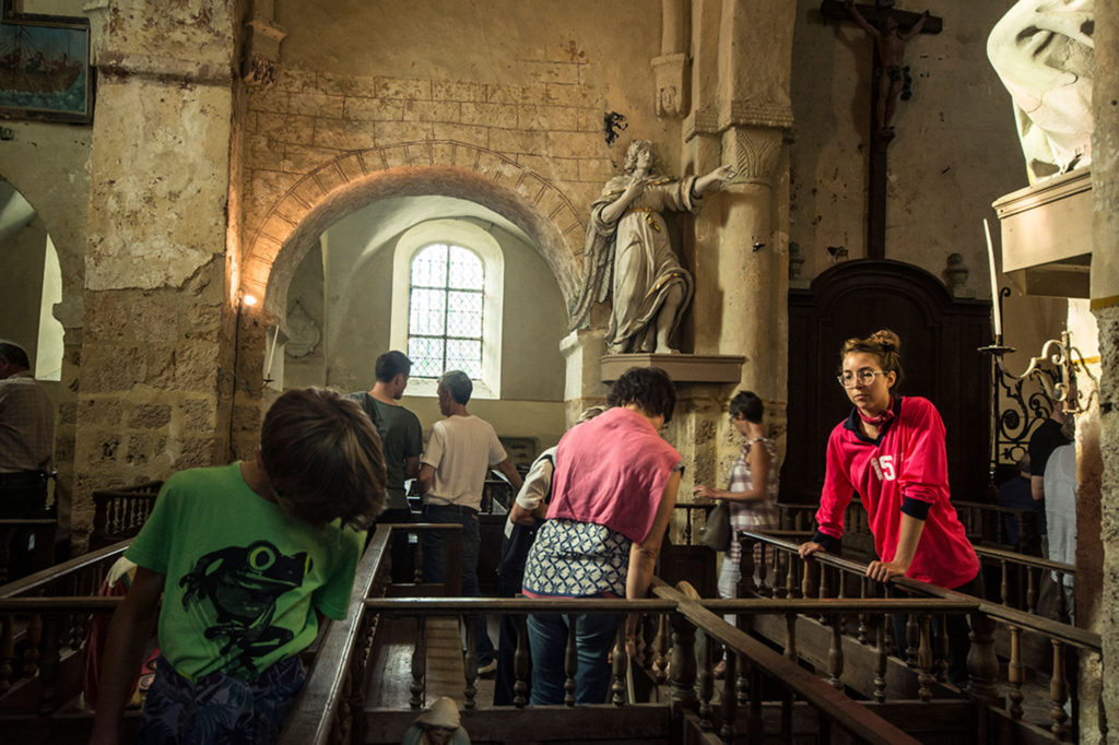 Viewers move around church pews to see the coupled drawings and sculptures -